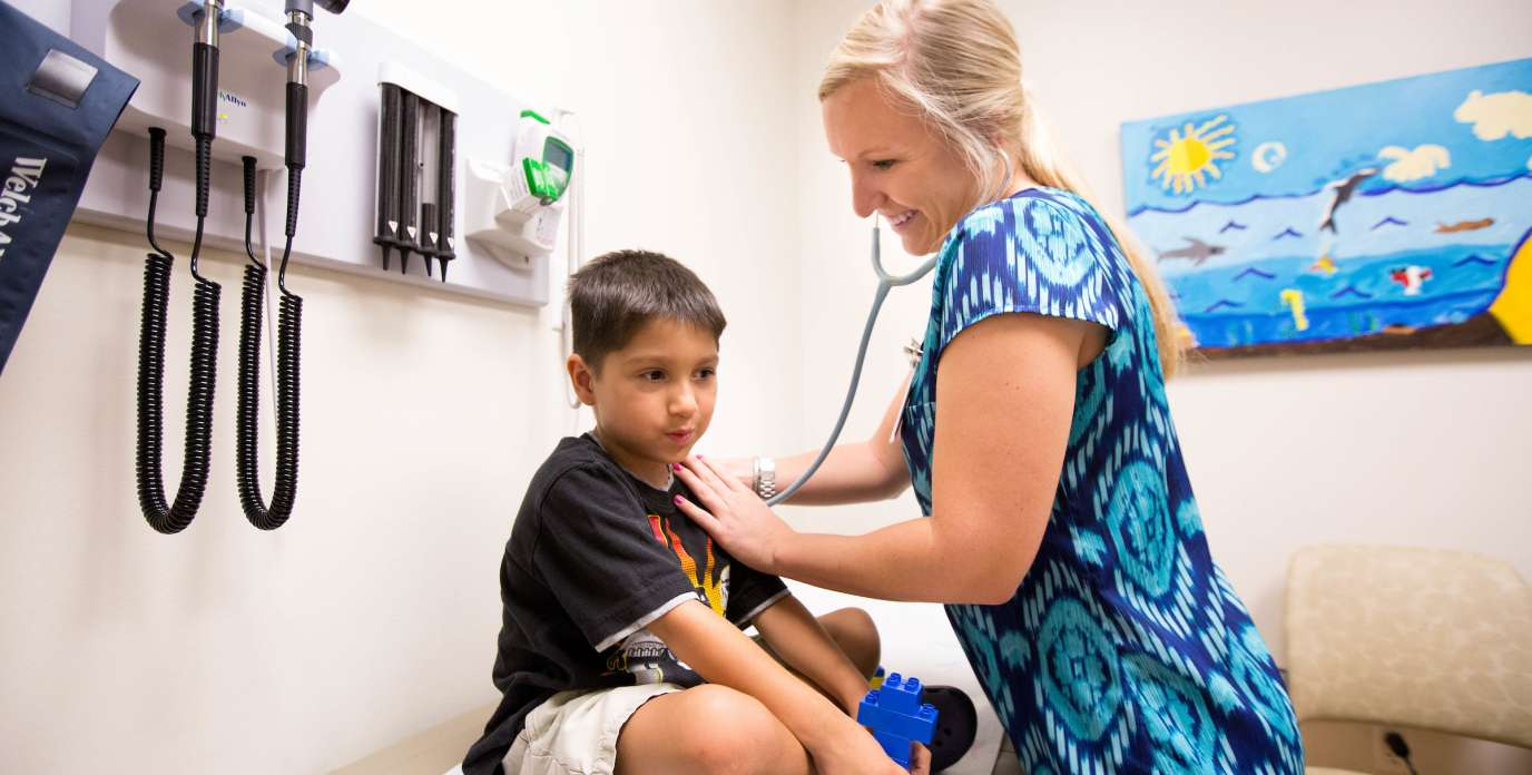 Nurse checking young male patients heart with stethoscope